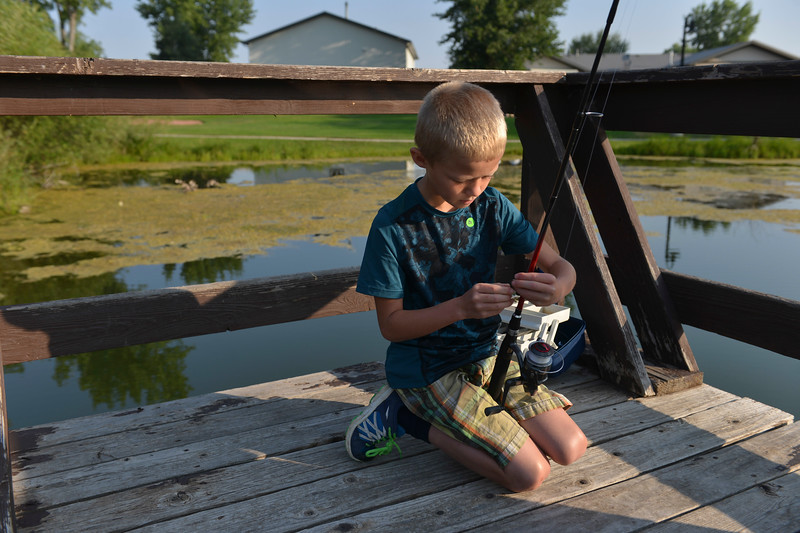 Justin Sheely | The Sheridan Press<br /> Eight-year-old Garrett Williamson baits his line during the annual Fishing Derby at Rotary Pond in Ranchester Saturday, Aug. 4, 2018. The Tongue River Valley Community Center hosted the fishing derby for children under 13 and under. Children competed for most fish caught and biggest catch to win prizes.