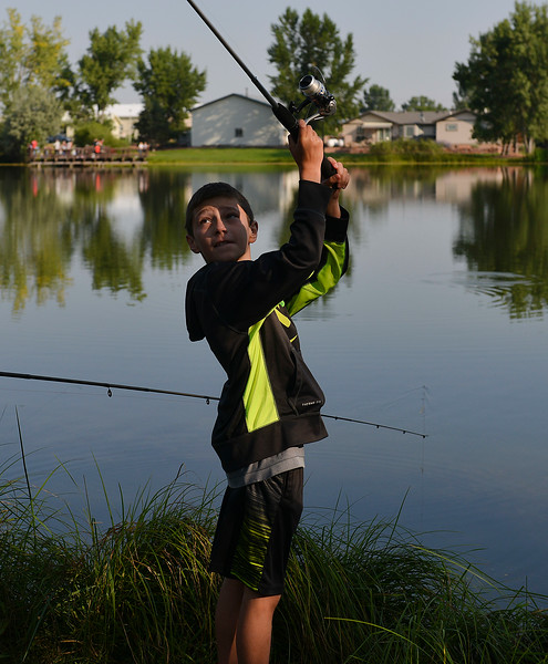 Justin Sheely | The Sheridan Press<br /> Nine-year-old Quin Petty looks back as he casts his line during the annual Fishing Derby at Rotary Pond in Ranchester Saturday, Aug. 4, 2018. The Tongue River Valley Community Center hosted the fishing derby for children under 13 and under. Children competed for most fish caught and biggest catch to win prizes.