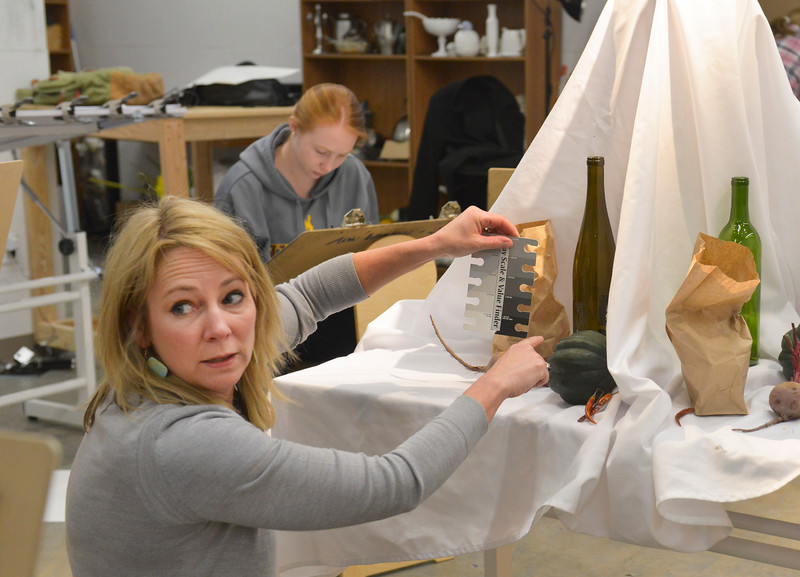 Justin Sheely | The Sheridan Press<br /> <br /> Art teacher Arin Waddell holds a grey value card against props as she explains to a student how to find values during Drawing 1 class at the Whitney Center for the Arts Thursday, Feb, 15, 2018.