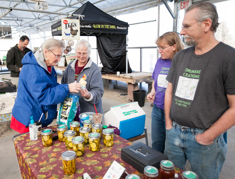 Tibby McDowell | The Sheridan Press<br /> Elizabeth Orum and Melba Jenkins, left, prepare a sample for the booth that Toni and Ray Zaske, right, run for their business Zorumske Creations, during the local food market at Landon's Greenhouse Saturday, March 3, 2018.