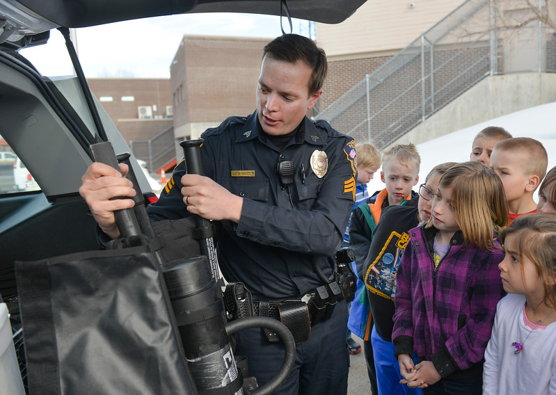 Justin Sheely | The Sheridan Press<br /> Sgt. James Hill pulls out a breach kit from the back of his car as Big Horn students look on during the YMCA's Funday Friday tour at Sheridan Police Department, March 2, 2018.