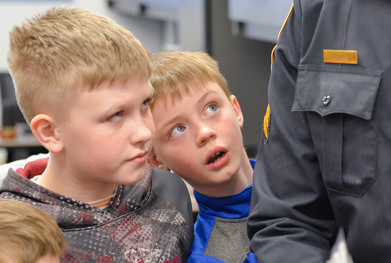 Justin Sheely | The Sheridan Press<br /> Big Horn Elementary fourth-grader Paul Lobdell, left, and third-grader Jackson Wallace look on as Sgt. James Hill shows the office during the YMCA's Funday Friday tour at Sheridan Police Department, March 2, 2018.