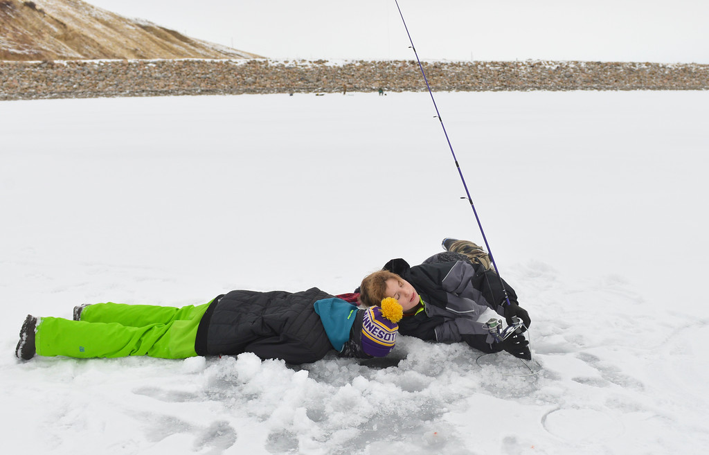 Justin Sheely   The Sheridan Press<br /> <br /> Twelve-year-old Caleb Kilbride, left, and David Betts look into an ice hold during ice fishing at Lake De Smet Friday, Feb. 2, 2018.