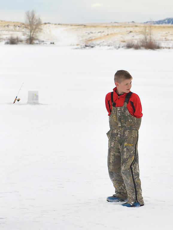 Justin Sheely   The Sheridan Press<br /> <br /> Nolan Bernard tucks his hands in during ice fishing at Lake De Smet Friday, Feb. 2, 2018.