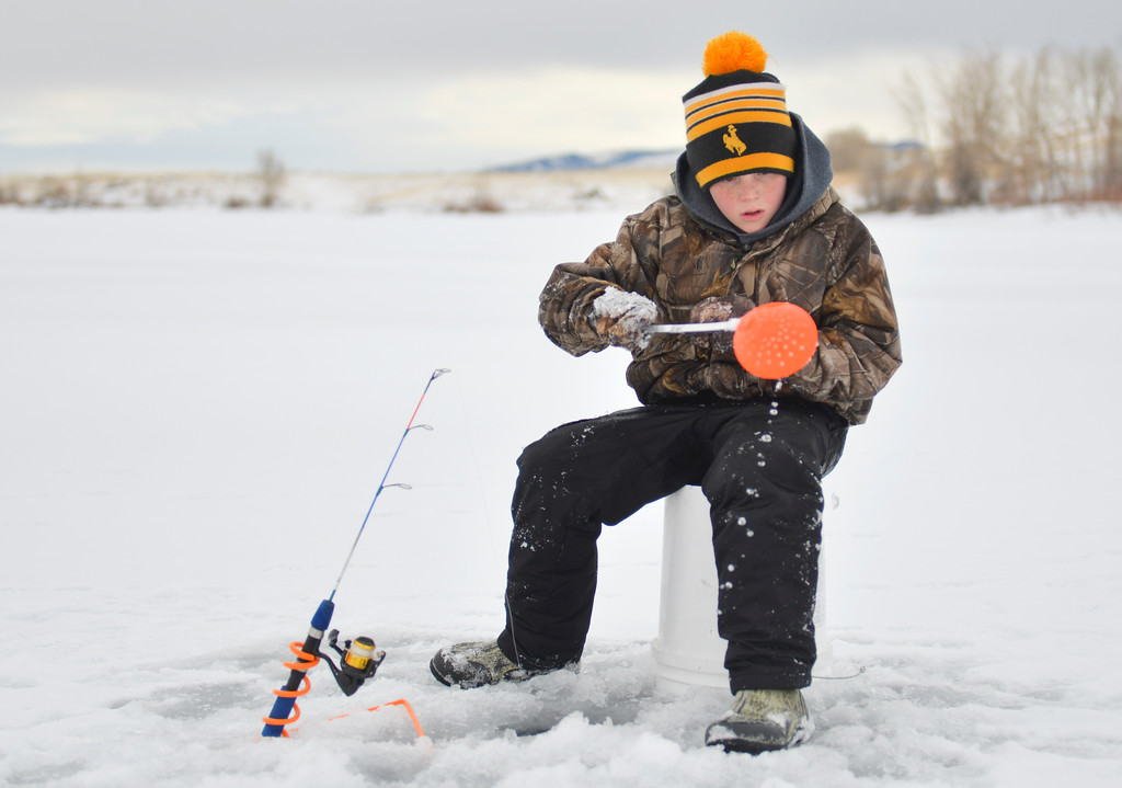Justin Sheely   The Sheridan Press<br /> <br /> Eleven-year-old Monty Walter scoops floaters out of his ice hole during ice fishing at Lake De Smet Friday, Feb. 2, 2018.