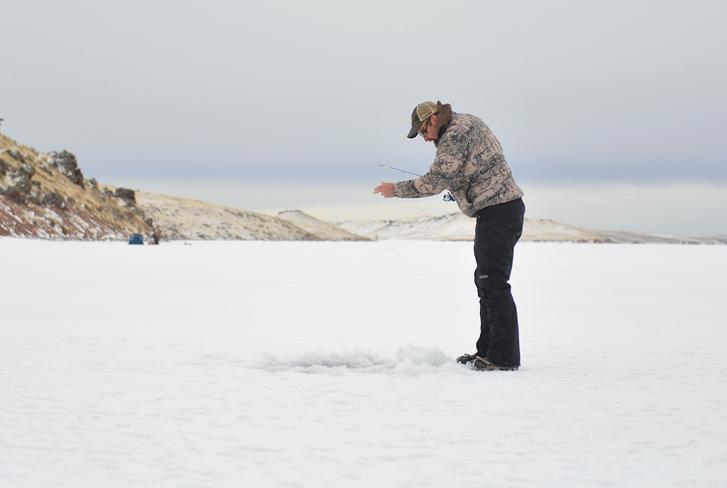 Justin Sheely   The Sheridan Press<br /> <br /> Matt McMeans check his line during ice fishing at Lake De Smet Friday, Feb. 2, 2018.