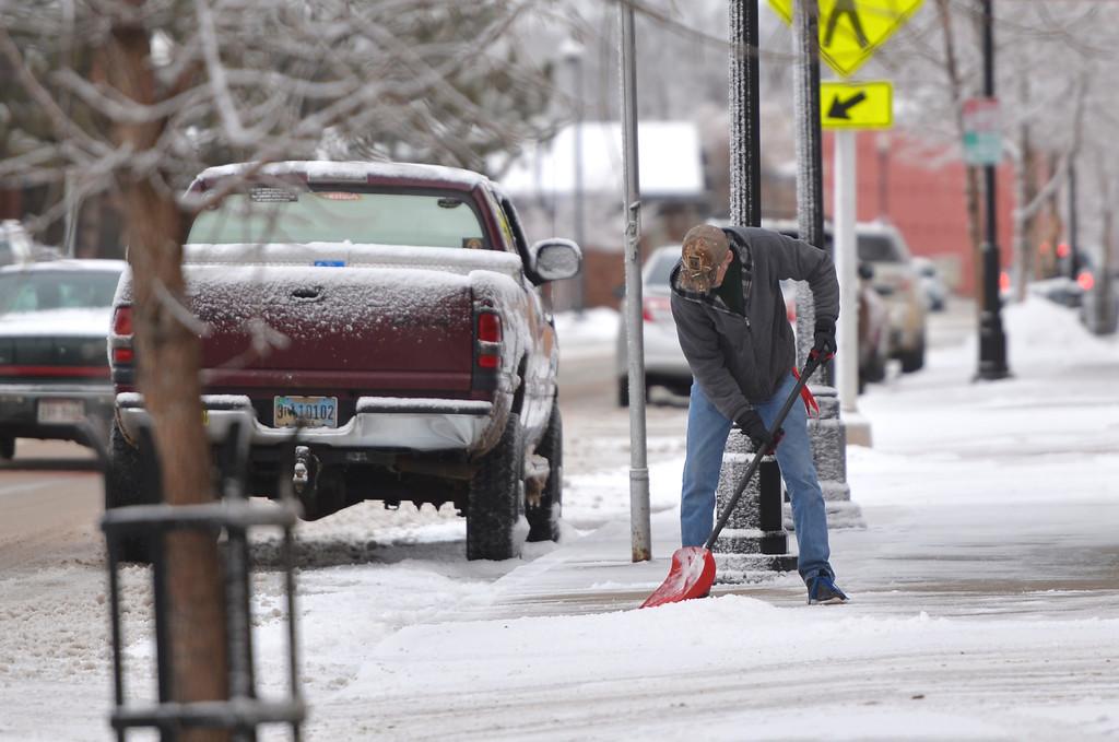Justin Sheely   The Sheridan Press<br /> <br /> A man shovels the sidewalk on Brooks Street Wednesday, Jan. 31, 2018. Light snow overnight made slippery roads and sidewalks.