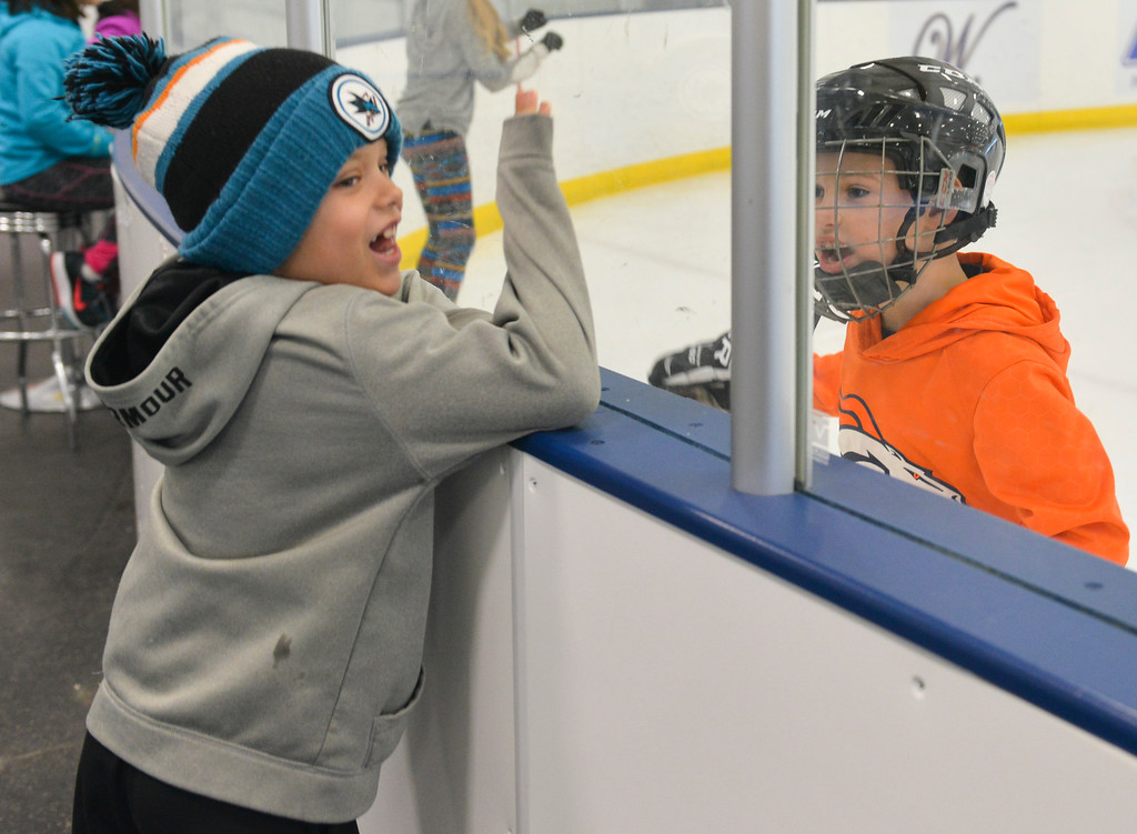 Justin Sheely   The Sheridan Press<br /> <br /> Connor Martinaeu, left, and Parker Reiger shout at each other through the glass during open skate at Whitney Rink at the M&M's Center Wednesday, Jan. 31, 2018.