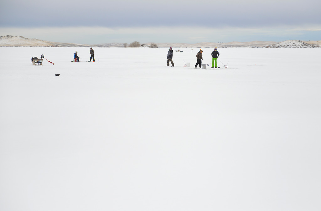 Justin Sheely   The Sheridan Press<br /> <br /> Children visit as they watch their lines during ice fishing at Lake De Smet Friday, Feb. 2, 2018.