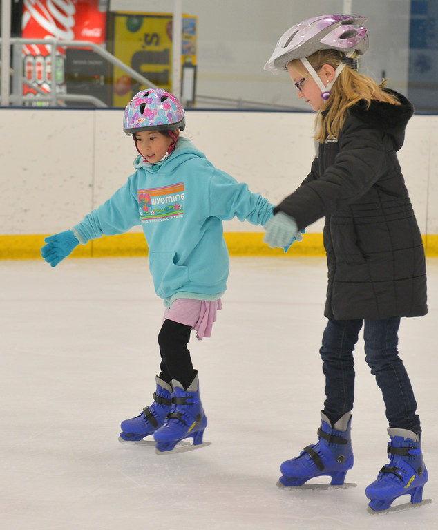 Justin Sheely   The Sheridan Press<br /> <br /> Meimei Boedecker, left, and Trinity Johnson skate together during open skate at Whitney Rink at the M&M's Center Wednesday, Jan. 31, 2018.