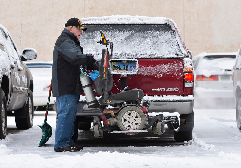 Justin Sheely | The Sheridan Press<br /> <br /> Korean war veteran Lee Hammett loads his motor chair after brushing off his truck in Sheridan Wednesday, Jan. 31, 2018. Light snow overnight made slippery roads and sidewalks.