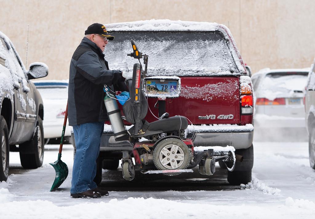 Justin Sheely   The Sheridan Press<br /> <br /> Korean war veteran Lee Hammett loads his motor chair after brushing off his truck in Sheridan Wednesday, Jan. 31, 2018. Light snow overnight made slippery roads and sidewalks.
