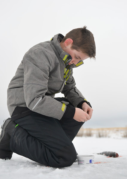 Justin Sheely | The Sheridan Press<br /> <br /> Thirteen-year-old Jaden Bernard changes bait on his line during ice fishing at Lake De Smet Friday, Feb. 2, 2018.