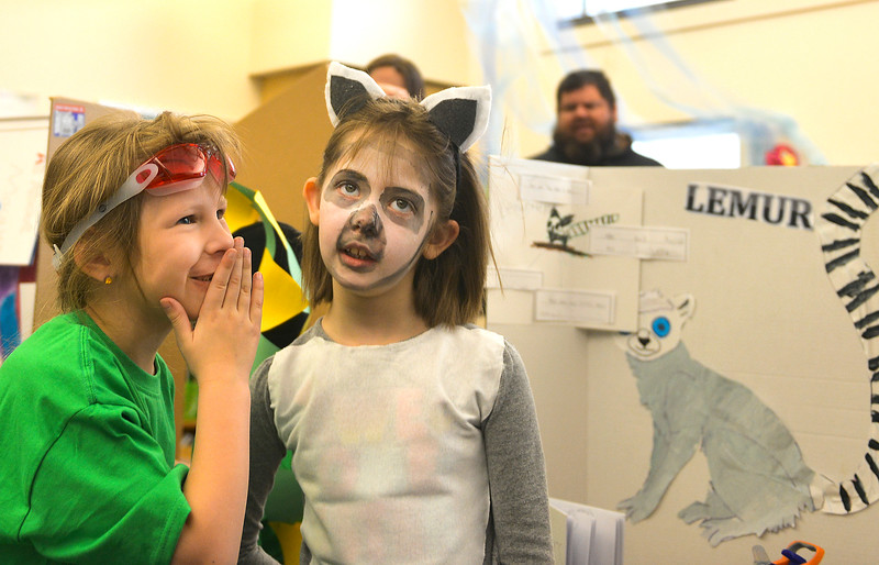 Justin Sheely | The Sheridan Press<br /> <br /> First graders Maira Ferguson, left, whispers to Piper Ferrier during the Animal Wax Museum event at Woodland Park Elementary School Friday, Feb. 9, 2018. First-grade students researched animals and gave a presentation on their findings through display boards, report books and costumes.