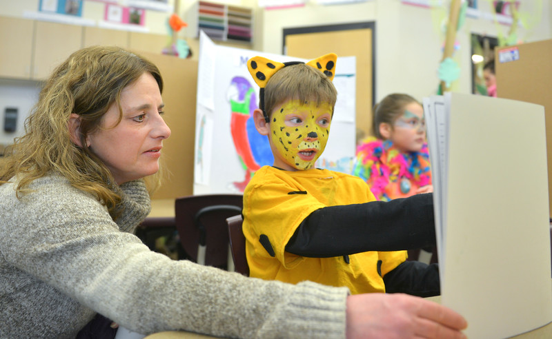 Justin Sheely | The Sheridan Press<br /> <br /> First-grade student Alecs Carroll, as a jaguar, presents his report to his mother Lexie Carroll during the Animal Wax Museum event at Woodland Park Elementary School Friday, Feb. 9, 2018. First-grade students researched animals and gave a presentation on their findings through display boards, report books and costumes.