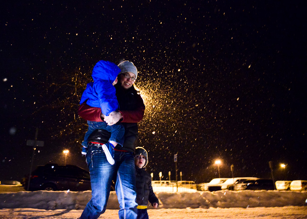 Justin Sheely | The Sheridan Press<br /> Sam Gibbons carries her son Cade Gibbons, 1, with his brother Oliver Gibbons, 2, through a snowy parking lot during the Broncs basketball game at Sheridan High School Friday, Jan. 12, 2018.