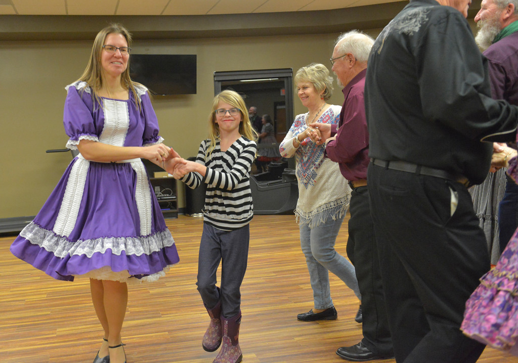 Justin Sheely | The Sheridan Press<br /> Christa Grywusiewicz, left, and Josie Yapunich, 10, hold hands during the weekly Jeans and Queens square dance night at the Hub on Smith Saturday, Jan. 13, 2018. The square dance club meets every Tuesday evening at the Hub on Smith for lessons, which are open and free for first time dancers.