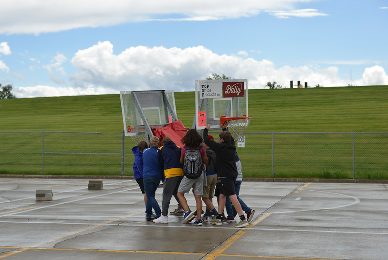 Justin Sheely | The Sheridan Press<br /> High school students carry a backboard set to a court during set up for the annual Wyoming Rehab Hoop Jam at Sheridan High School Friday, June 1, 2018.