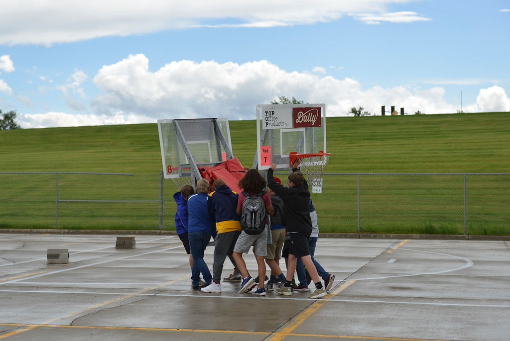 Justin Sheely   The Sheridan Press<br /> High school students carry a backboard set to a court during set up for the annual Wyoming Rehab Hoop Jam at Sheridan High School Friday, June 1, 2018.