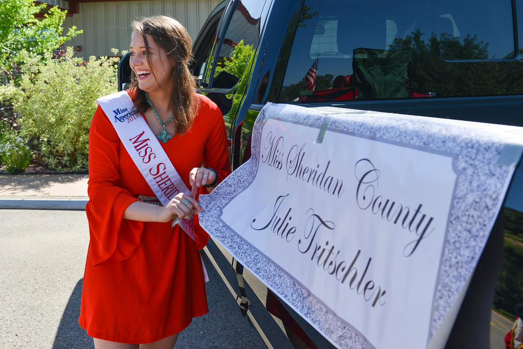 Justin Sheely | The Sheridan Press<br /> Miss Sheridan County Julie Tritschler tapes up her banner to the truck during the second annual Hay Daze in Ranchester Saturday, June 9, 2018.
