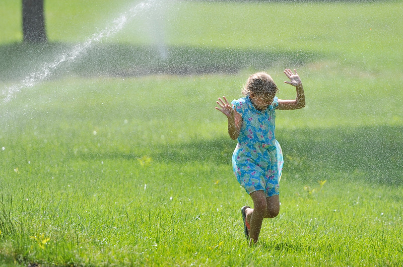 Justin Sheely | The Sheridan Press<br /> Seven-year-old Aubriee Haskett runs through a spraying sprinkler at Kendrick Park Wednesday, June 6, 2018.