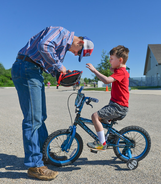 Justin Sheely | The Sheridan Press<br /> Kyle Porter, left, adjusts a bike helmet for his son Boone Porter, 5, during the Make Room Bike-A-Thon at First Baptist Church Saturday, June 2, 2018. The event supported the Summer of Hope program, which brings orphan children from around the world to host families in the United State for the summer.