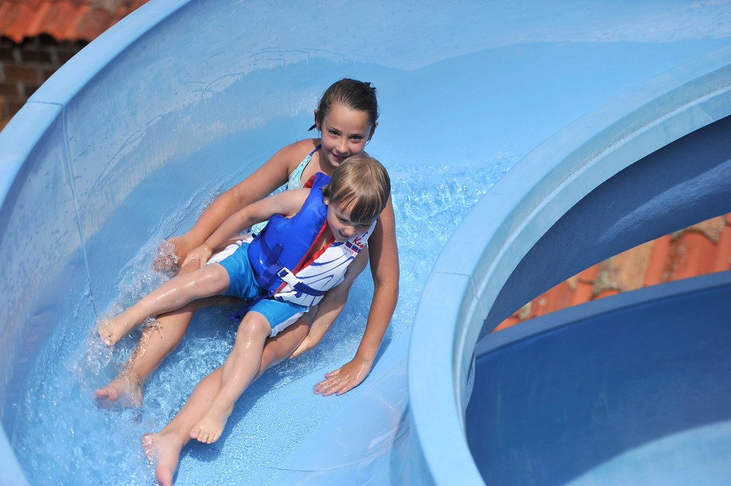 Justin Sheely | The Sheridan Press<br /> Nine-year-old Avery Nikirk takes her younger brother Archer Nikirk down the slide at Kendrick Pool Thursday, June 7, 2018. Kendrick Pool open swim is daily from 1 p.m. to 7 p.m. Children 2 years and under are free.