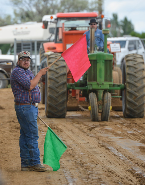 Justin Sheely | The Sheridan Press<br /> Caleb Green waits to signal a competitor during the antique tractor pull at the Sheridan County Fairgrounds Saturday, June 16, 2018. 28 Antique tractor owners from the region took the challenge of the tractor pull, which involved pulling a sled with a nearly 10,000 lbs load across a dirt track 220 feet for a full pull.