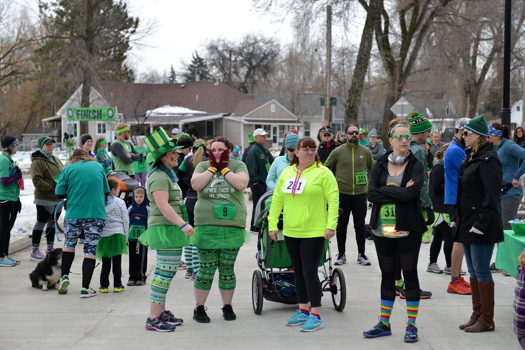 "Justin Sheely | The Sheridan Press<br /> Race participants visit at the registration area during the Sheridan Jaycees' annual ""Run 'Till your Green"" fun run/walk at Kendrick Park Saturday, March 17, 2017."