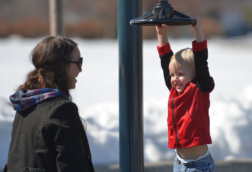 Justin Sheely  | The Sheridan Press<br /> Bridget Brinkerhoff, left, watches as her son Brock Brinkerhoff, 2, spins on playground equipment at Whitney Commons Park Tuesday, March 13, 2018. Wednesday will be sunning with a high of 53 degrees, chances of rain and snow are expected Thursday and Friday.