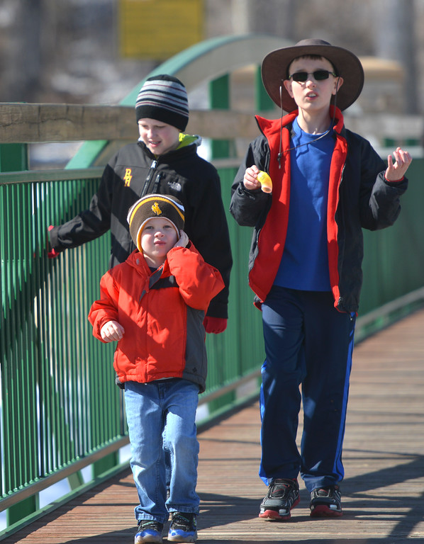 Justin Sheely  | The Sheridan Press<br /> Children, from left, Paul Lobdell, 6, and Carson Norling walk across the Goose Creek with Danny Lobdell, front, 4, at Kendrick Park Tuesday, March 13, 2018. Wednesday will be sunning with a high of 53 degrees, chances of rain and snow are expected Thursday and Friday.