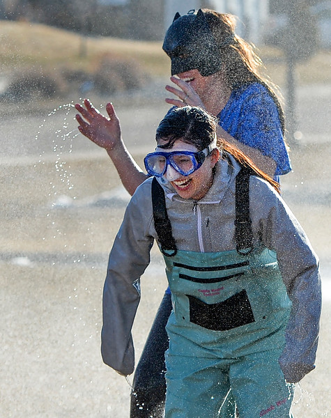 Justin Sheely | The Sheridan Press<br /> Woodland Park teachers Jessica Sparks, front, and Kristie Garriffa react as they are spray by a fire hose at Woodland Park Elementary School Tuesday, March 20, 2018. Several Woodland Park teachers were sprayed down by a fire hose in celebration of their classrooms raising $80 in a penny drive for the Wyoming Special Olympics.