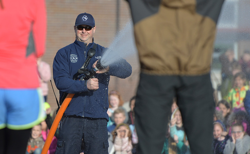 Justin Sheely | The Sheridan Press<br /> Sheridan Fire-Rescue firefighter Gerald Johnston opens the fire hose as teacher line up at Woodland Park Elementary School Tuesday, March 20, 2018. Several Woodland Park teachers were sprayed down by a fire hose in celebration of their classrooms raising $80 in a penny drive for the Wyoming Special Olympics.