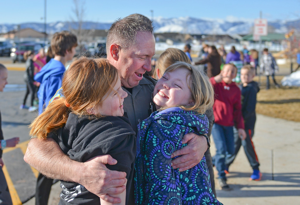 Justin Sheely | The Sheridan Press<br /> Sheridan County Sheriff's Office deputy Boot Hill receives hugs from fifth-graders Cambia Shultz, left, and Ceda Clearwater at Woodland Park Elementary School Tuesday, March 20, 2018. Deputy Hill, along with several Woodland Park teachers were sprayed down by a fire hose in celebration of their classrooms raising $80 in a penny drive for the Wyoming Special Olympics.