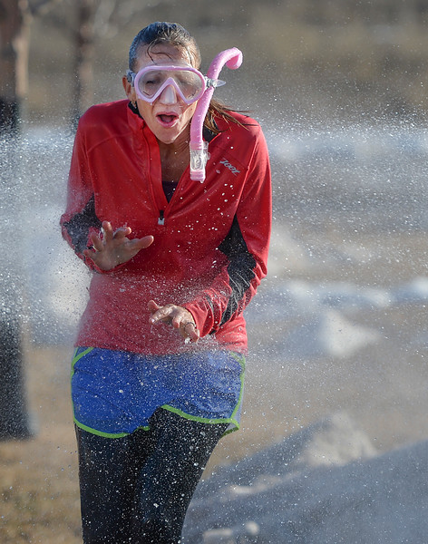 Justin Sheely | The Sheridan Press<br /> School principal Paige Sanders runs past a stream of water at Woodland Park Elementary School Tuesday, March 20, 2018. Several Woodland Park teachers were sprayed down by a fire hose in celebration of their classrooms raising $80 in a penny drive for the Wyoming Special Olympics.
