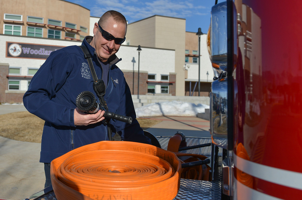 Justin Sheely | The Sheridan Press<br /> Sheridan Fire-Rescue firefighter John Syring connects a hose to the fire engine at Woodland Park Elementary School Tuesday, March 20, 2018. Several Woodland Park teachers were sprayed down by a fire hose in celebration of their classrooms raising $80 in a penny drive for the Wyoming Special Olympics.
