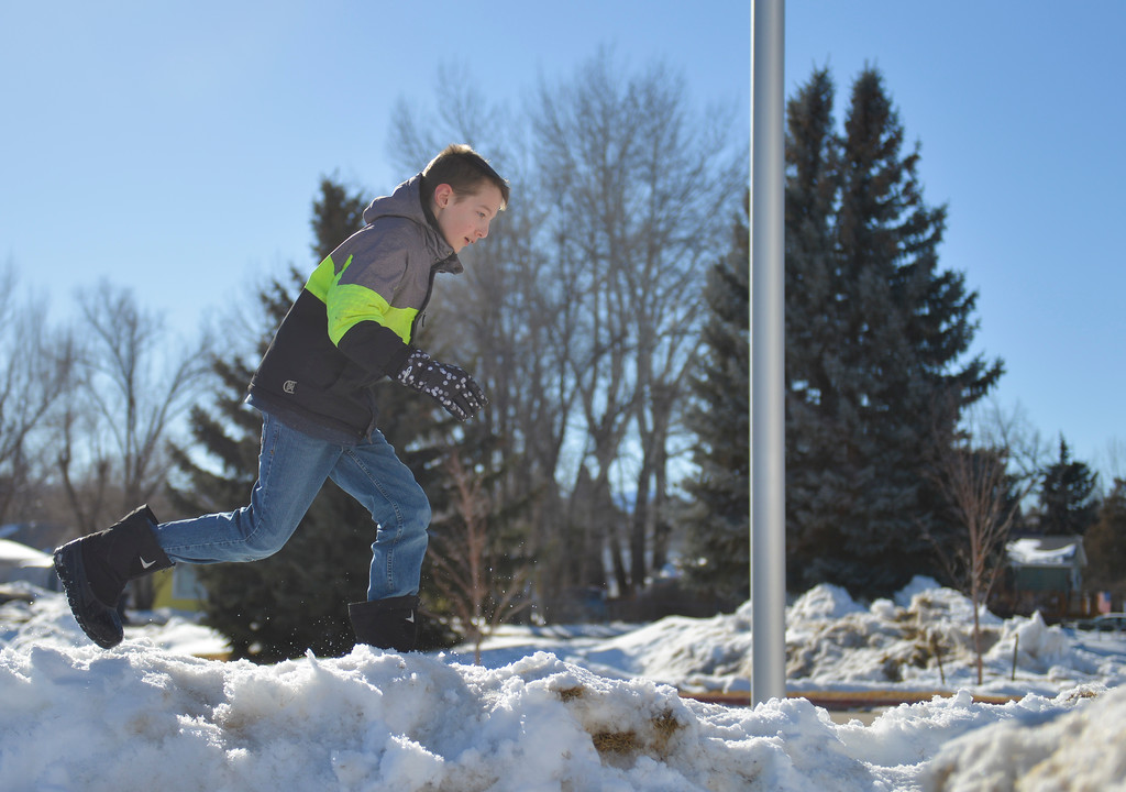 Justin Sheely | The Sheridan Press<br /> Jackson Gaskill plays on a pile of snow outside Coffeen Elementary School Wednesday, March 7, 2018.