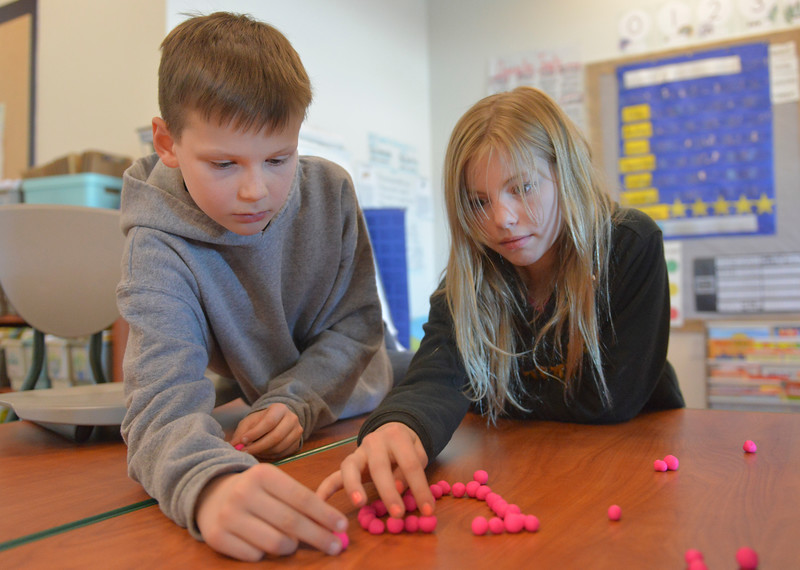 Justin Sheely | The Sheridan Press<br /> Fifth-graders Aedan Willis, left, and Samantha Glassinger move lumps of playdough in place for a stop motion video during an after school program at Coffeen Elementary School Wednesday, March 7, 2018. The students created a channel on Youtube to upload their stop motion animation short videos.