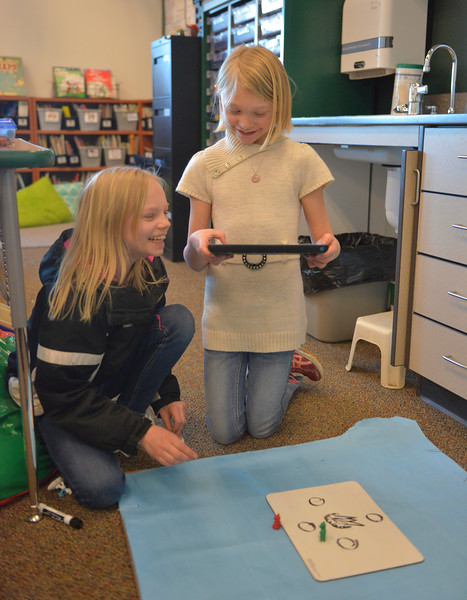 Justin Sheely | The Sheridan Press<br /> Fourth-grader Jade Wunder, left, moves pieces as Caylee Ross, third-grade, records stop motion animation on an iPad during an after school program at Coffeen Elementary School Wednesday, March 7, 2018. The students created a channel on Youtube to upload their stop motion animation short videos.