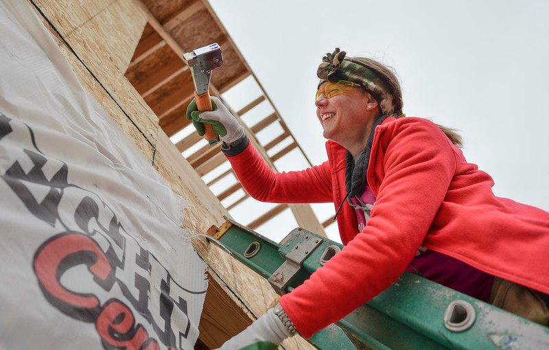 Justin Sheely | The Sheridan Press<br /> Volunteer Kandy Jensen staples a house wrap during the Thrivent Women Build day at the Habitat for Humanity homes in the Poplar Grove subdivision in Sheridan Saturday, May 19, 2018.