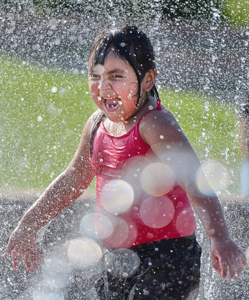 Justin Sheely | The Sheridan Press<br /> Five-year-old Shaylee Andreas shouts in the water fountain at Whitney Commons Park Tuesday, May 15, 2018. The fountain is on daily from 11 a.m. to 6 p.m. Summer hours extend the operation of the fountain to 10 p.m.