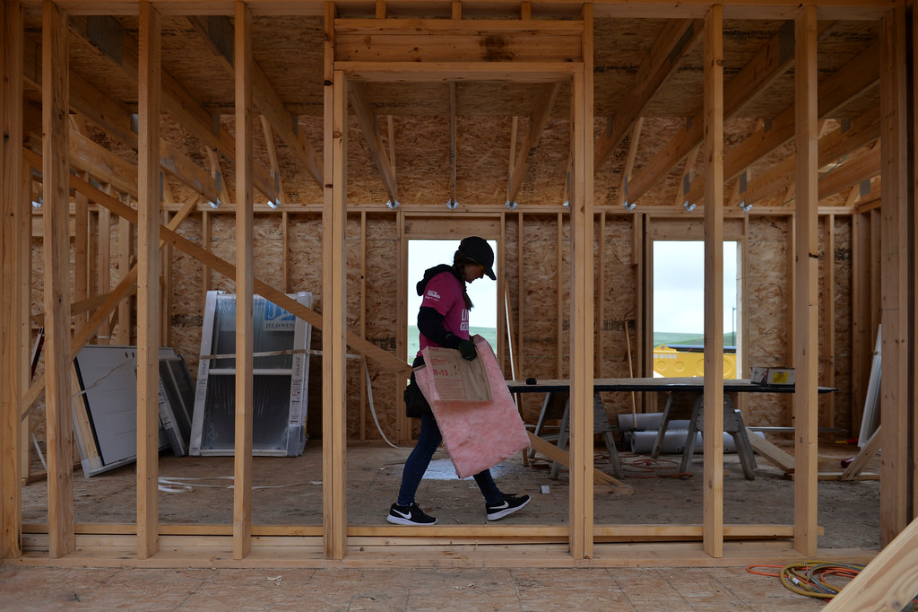 Justin Sheely | The Sheridan Press<br /> A woman carries scraps out of the job site during the Thrivent Women Build day at the Habitat for Humanity homes in the Poplar Grove subdivision in Sheridan Saturday, May 19, 2018.