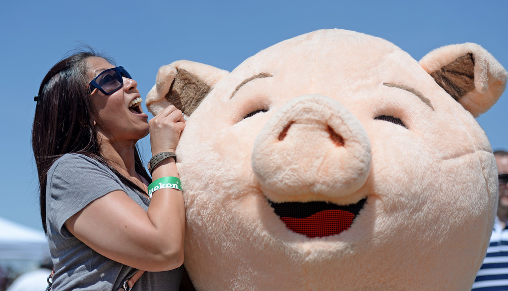 . Coleen Pila of Long Beach pretends to nibble on Pork Chops ear at  the West Coast BBQ Classic  in Long Beach, CA. on Saturday May 10, 2014. (Photo by Sean Hiller/ Daily Breeze).