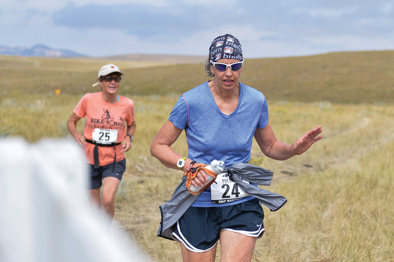Ashleigh Fox | The Sheridan Press<br> Martha Robison, right, and Stacey Page run through the gate at the last aid station during the Wolf Creek Wrangle Saturday, Sept. 15, 2018. Page finished eighth and Robison finished ninth in the half marathon.