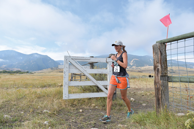 Ashleigh Fox | The Sheridan Press<br> Rebecca Zisch of Cheyenne runs through the gate at the last aid station during the Wolf Creek Wrangle Saturday, Sept. 15, 2018. Zisch earned a fifth place finish overall in the half marathon.