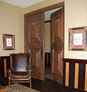 Custom made doors from old wood from Brazil, aged leather wingback armchair, wood panelling waistcoat throughout.