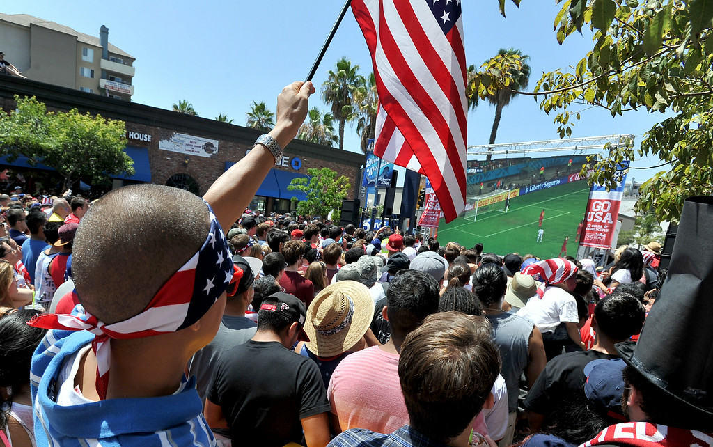 . Jose Gomez of Bell Gardens watch the jumbo screen on Pine Avenue to watch the United States play Belgium in the World Cup Soccer game in Long Beach CA. on Tuesday July 01, 2014. (Photo by Sean Hiller/ Daily Breeze).