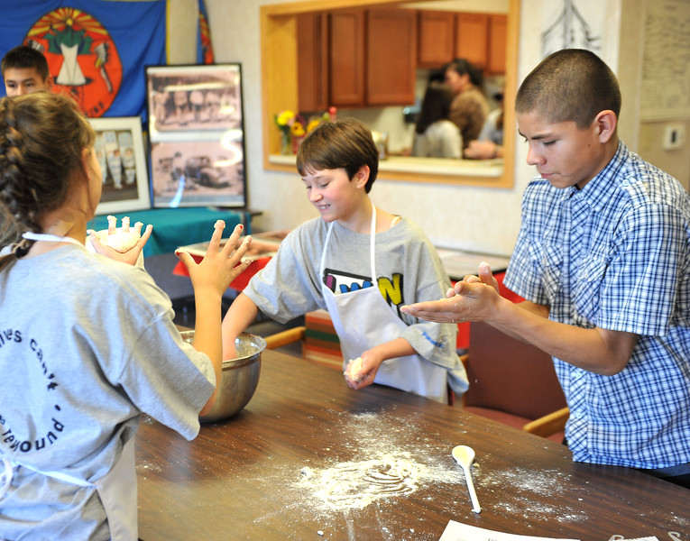 Ryan Patterson | The Sheridan Press<br /> From left: Sheridan Junior High School sixth-graders Mackenzie Thorson, Macie Geis and Wyola School eighth-grader AJ Foote roll dough during a cultural event at the Art Culture and Elder's Center in Wyola, Montana, Tuesday, Nov. 20, 2018. About 15 students from each school spent more than two hours doing several different activities.