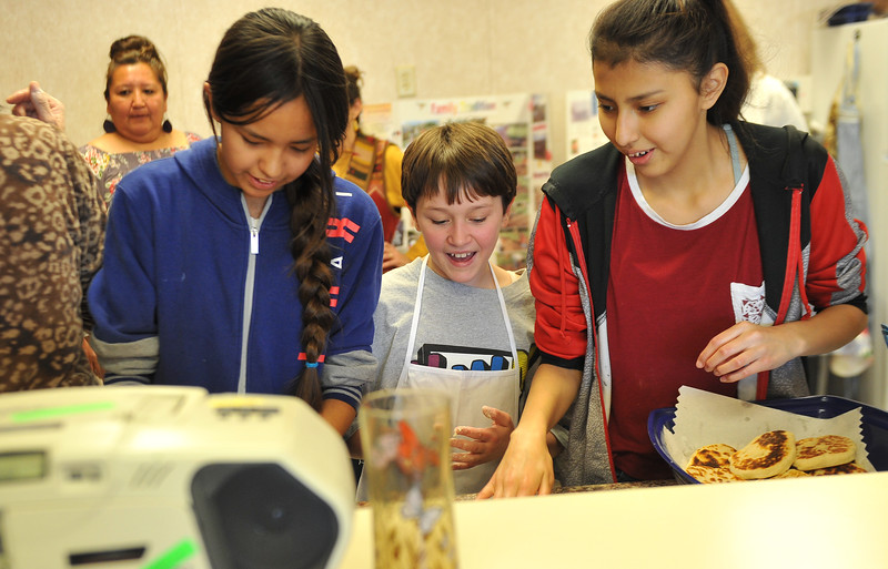 Ryan Patterson | The Sheridan Press<br /> From left: Wyola School eighth-grader Marajah Pease, Sheridan Junior High School sixth-grader Macie Geis and Wyola School eighth-grader Varsha Takes Enemy make pan bread during a cultural event at the Art Culture and Elder's Center in Wyola, Montana, Tuesday, Nov. 20, 2018. About 15 students from each school spent more than two hours doing several different activities.