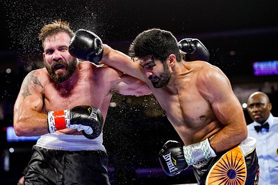 VIJENDER SINGH (black, orange, and grey trunks) and MICHAEL SNIDER battle in a super middleweight bout at the Prudential Center in Newark, New Jersey.